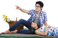 Couple sitting on mat and look at something Stock Photo