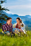 Couple is sitting in the meadow with mountain Stock Photo
