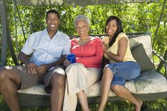 Couple Sitting With Mother On Swing Stock Photos