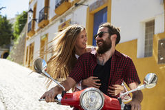 Couple sitting on motor scooter looking at each other, Ibiza Stock Photo