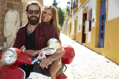 Couple sitting on motor scooter, looking to camera, Ibiza Royalty Free Stock Photos