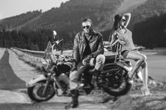 Couple sitting on a motorbike. Handsome men wearing leather jacket, gloves and boots and sexy girl wearing shorts. Summer day in the mountains. Tilt shift lens Royalty Free Stock Photos