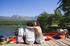 Couple sitting beside motorboat on lake jetty, woman embracing man, looking over shoulder, smiling, rear view, portrait Royalty Free Stock Images