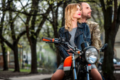 Couple sitting on the motorcycle in the city park Royalty Free Stock Photos