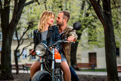 Couple sitting on the motorcycle in the city park Royalty Free Stock Photo