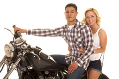 Couple sitting on motorcycle close western serious Royalty Free Stock Images