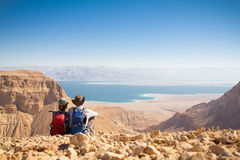Couple sitting mountain above sea. Couple sitting stone desert mountain edge above sea. Dead sea, Judea mountains, Israel stock image