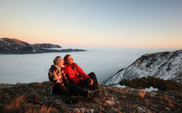 Couple sitting on a mountain at sunset in winter Stock Image