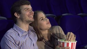 Sweet couple watching romantic comedy at the cinema. A couple is sitting in a movie theater and watching a movie. They embrace. The guy and the girl eat popcorn stock footage