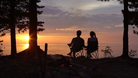 Couple is Sitting near Campfire at Night.