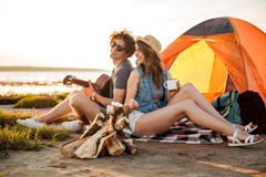 Couple sitting near campfire and playing guitar. Happy young couple sitting near campfire and playing guitar Stock Photography