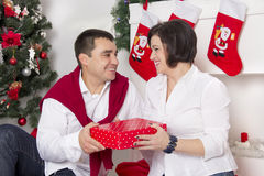 Couple sitting near the Christmas fireplace Royalty Free Stock Image