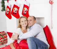 Couple sitting near the Christmas fireplace Royalty Free Stock Photos
