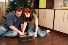 Couple sitting near Christmas tree with laptop Stock Photo