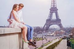 Couple sitting near Eiffel Tower in Paris, honeymoon in Europe. Romantic love, affectionate couple sitting near Eiffel Tower in Paris, honeymoon in Europe royalty free stock photography