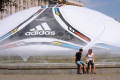 Couple sitting near EURO 2012 ball Royalty Free Stock Photo