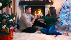Couple sitting near fireplace, drinking champagne stock video footage