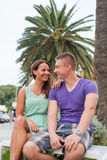 The couple sitting near the palm tree and spending great time. Stock Photo