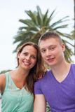 The couple sitting near the palm tree and spending great time. Stock Photos