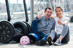 Couple sitting near segways at sea front Stock Photo