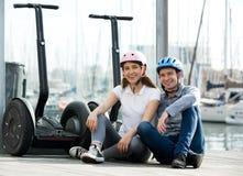 Couple sitting near segways at sea front Stock Image