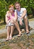 Couple sitting near stream stock photo