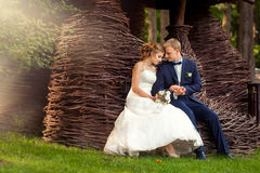 Couple sitting near summer arbor. Wedding couple sitting near summer arbor made of twigs Royalty Free Stock Photography