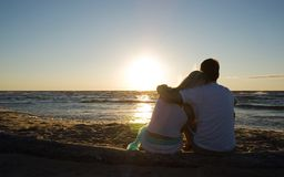 Free Couple Sitting Near The Sea On Sunset Royalty Free Stock Photography - 11978757