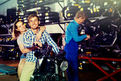 Couple sitting on new motorbike in workshop Stock Images
