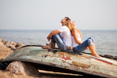 Couple sitting on old boat. Back to back Stock Images