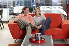 Couple Sitting On New Red Sofa In Furniture Store, Man Glancing At Woman, Smiling, Portrait Stock Photos