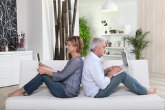 Couple Sitting On Sofa Royalty Free Stock Photos