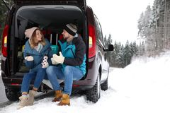 Couple sitting in open car trunk full of luggage near road, space for text. Winter. Vacation stock photography
