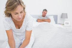 Couple sitting on opposite ends of bed after a fight royalty free stock images