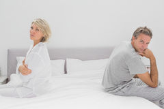 Couple sitting on opposite sides of bed looking at camera Stock Images