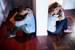 Couple sitting on opposite sides of the wall Stock Images