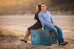 Couple sitting outdoors back to back Royalty Free Stock Photography
