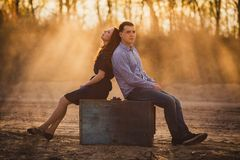 Couple sitting outdoors back to back Royalty Free Stock Images