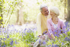 Couple sitting outdoors with flowers smiling. At each other Stock Images