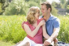 Couple sitting outdoors holding flower smiling Stock Photo
