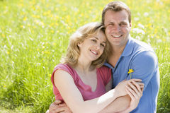 Couple sitting outdoors holding flower smiling royalty free stock photography