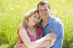 Couple sitting outdoors holding flower smiling royalty free stock images