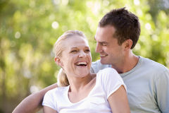 Couple sitting outdoors laughing Stock Images