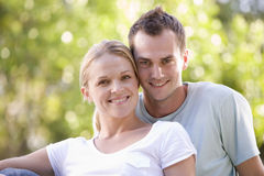 Couple sitting outdoors smiling Stock Photography