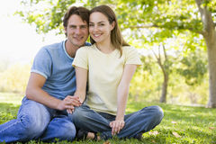 Couple sitting outdoors smiling Royalty Free Stock Images