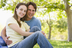 Couple sitting outdoors smiling Stock Photos