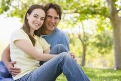 Couple sitting outdoors smiling stock photos