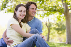 Couple sitting outdoors smiling Stock Images