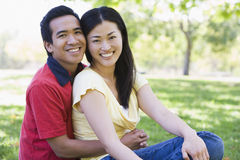 Couple sitting outdoors smiling. With tree in background Royalty Free Stock Image