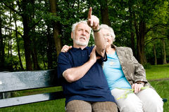 Couple sitting outside on a park bench Stock Images